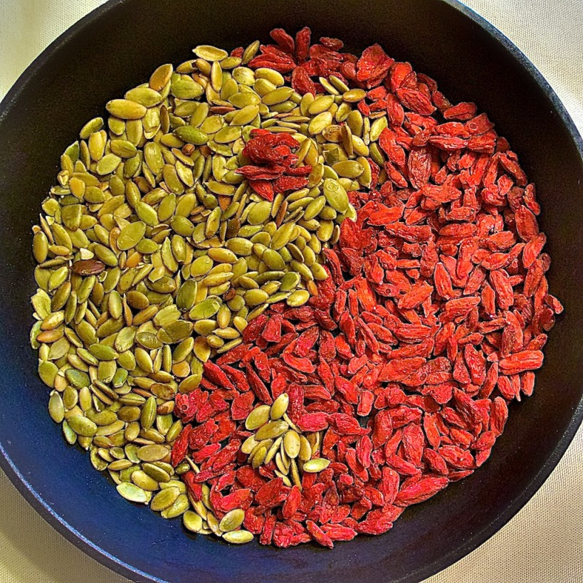 Yng Yang symbol made out of pumpkin seeds and Goji berries (displayed in a cast iron skilled).